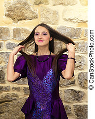 Beautiful fashion girl on background of the stone wall