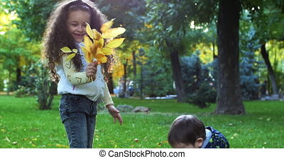 Beautiful Fashion Happy Smiles Stylish Joyful European Little Cute Brother and Sister Have Fun Walking in Autumn Park, Happy to Play with Autumn Foliage, Boy Gives a Bouquet of Leaves to His Beloved Sister, Girl Kisses His Little Brother. Family concept. 4K
