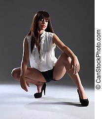 Beautiful fashion model in sexy pose and pout - Long legs in...