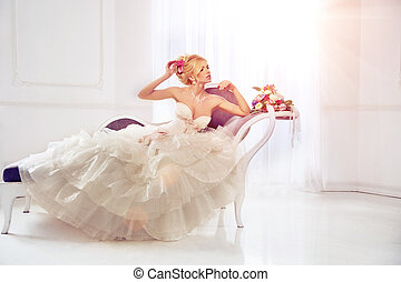 Beautiful fashion model. Sensual bride. Woman with wedding dress, hair and make up. Waiting for groom on background of window Blue eyes. Natural manicure. Beauty spring girl with bouquet of flowers in hands