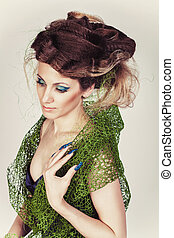 Beautiful Fashion Model with Big Hairstyle in green mesh and blue dress. Woman with long blue nails