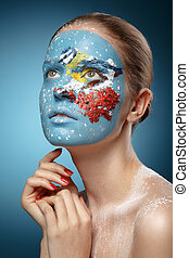 Beautiful fashion model with face art in winter style. Textural makeup. Tit on a branch of rowan.
