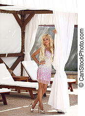 Beautiful fashion sexy blonde model woman with long wavy hair in luxurious dress