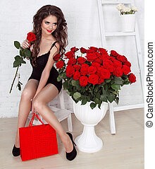 Beautiful fashion smiling girl with bouquet of roses and box gifts. Valentine's day. Happy brunette woman on holiday.