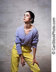 Beautiful fashion thinking woman posing and looking up in violet sweater and yellow pants on grey studio background. Portrait of european model.