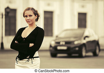 Beautiful fashion woman in black dress next to her car