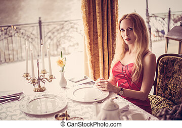 beautiful fashion woman in red dress in restaurant