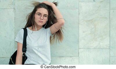 Beautiful fashion woman standing near bricks wall on the city street in grey coat. Brunette sexy girl with long hair and glasses near wall watch in camera.