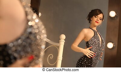 Beautiful fashion young girl in elegant black dress with makeup and hairstyle, attractive brunette posing in front of the mirror with light bulbs in the dressing room.