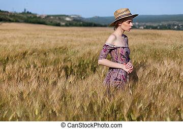 Beautiful fashionable blonde woman in a field of wheat