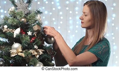 Beautiful fashionable girl in a green dress with red lips decorates the Christmas tree