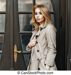 Beautiful fashionable girl in a light coat near the wooden door of the hotel