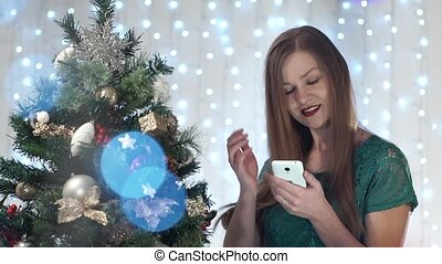 Beautiful fashionable girl in with red lips phone uses against the background dressed up Christmas tree.