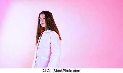 Beautiful fashionable girl poses on a pink background -...