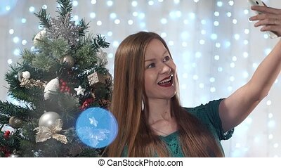Beautiful fashionable girl with red lips is photographed against the background dressed up Christmas tree