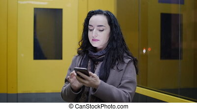 Beautiful Fashionable Happy Stylish Young Woman in Brown Coat with Dark Blue Scarf and Long Dark Curly Hair Enjoys Coffee Busy with her Mobile Phone While Walking a City Street. Pretty Girl Messaging on the Smart-phone on the background of the night or evening city. Close up portrait in 4K
