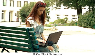 beautiful fashionable lady in the park with the laptop sits on a bench