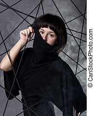 beautiful fashionable lady wearing a gothic black dress with high collar, poses in white smoke on a grey background.