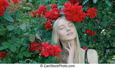 Beautiful fashionable portrait of a young woman with blue eyes and blonde hair in a outdoors in red rose garden