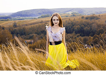 Beautiful fashionable pretty gorgeous girl in dress on the flowers field. Nice girl with wreath of flowers on her head and bouquet of many yellow flowers sitting on meadow yellow field in summertime.