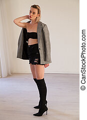 beautiful fashionable woman blonde in black boots with heel