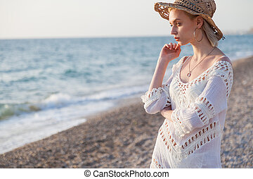 beautiful fashionable woman in white underwear and a hat on the Beach Ocean