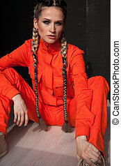 beautiful fashionable woman with braids in orange clothes