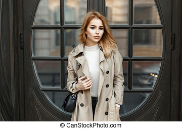 Beautiful fashionable young blonde girl in coat with bag near hotel door