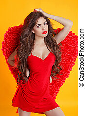 Beautiful female angel model posing with red wings in dress...