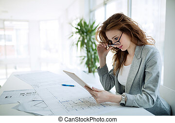 Beautiful female architect working in office