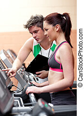 Beautiful female athlete standing on a running machine talking with her personal coach in a fitness center