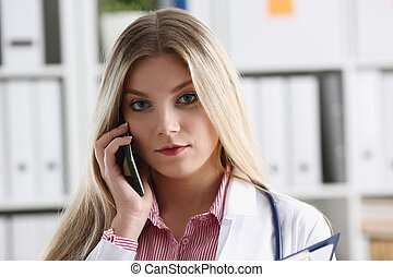 Beautiful female blond doctor talking on phone