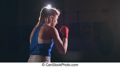 Beautiful female boxer conducts a fight with shadow while...