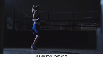 Beautiful female boxer jumping rope during active Boxing...
