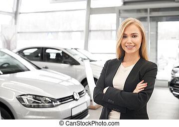 Beautiful female car dealer posing in dealership.