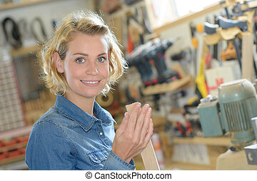 beautiful female carpenter in a workshop