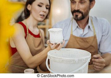 Beautiful female ceramist with dark nail art holding little...