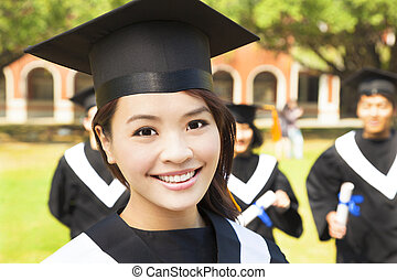 beautiful female college graduate with classmates at ceremony