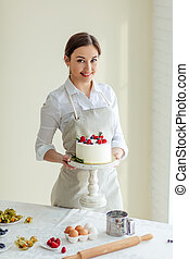 beautiful female confectioner looking at the camera