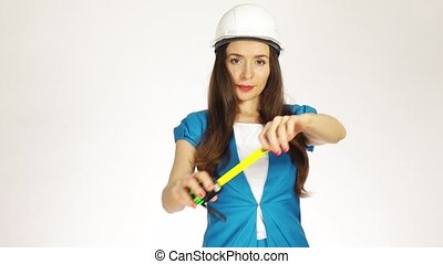 Beautiful female construction engineer or architect in hard hat using measure tape against white background. 4K shot