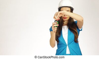 Beautiful female construction engineer using measure tape against white background