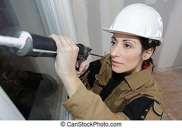 beautiful female construction worker using caulking gun at site