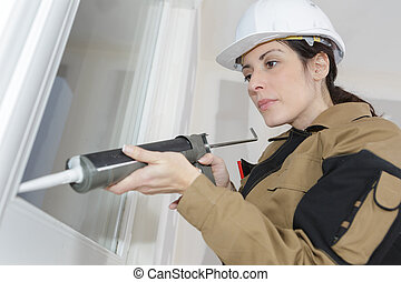 beautiful female construction worker using caulking gun
