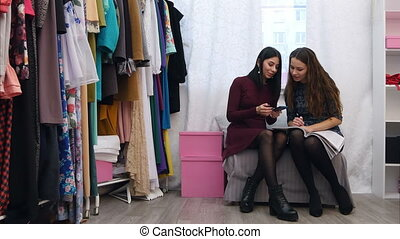Beautiful female customer show a dress she wants to order to boutique owner using cell phone