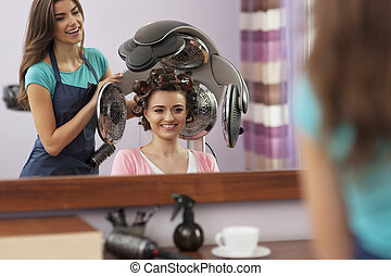 Beautiful female customer sitting under hair dryer with rollers