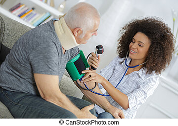 beautiful female doctor testing patients blood pressure