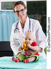 Beautiful female doctor with little baby patient