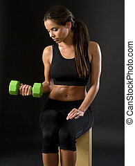 Beautiful female doing dumbbell curl
