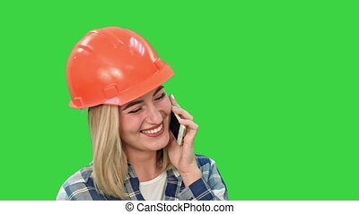 Beautiful female engineer in hardhat calling via cellphone on a Green Screen, Chroma Key.