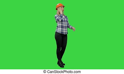 Beautiful female engineer in hardhat havin a phone call correcting the project on a Green Screen, Chroma Key.